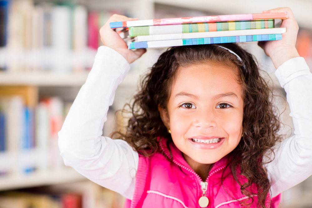 Happy girl at library holding books summer learning loss