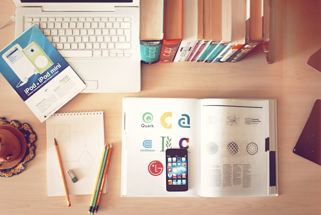 Student stationery on a desk including textbook, physics work, pencils, rubber, notebook, laptop and books